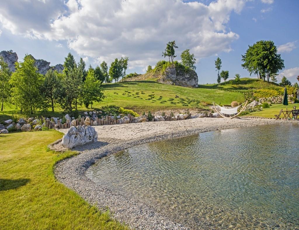 Idealnie wkomponowany w krajobraz, sztucznie zbudowany, ozdobny staw kąpielowy